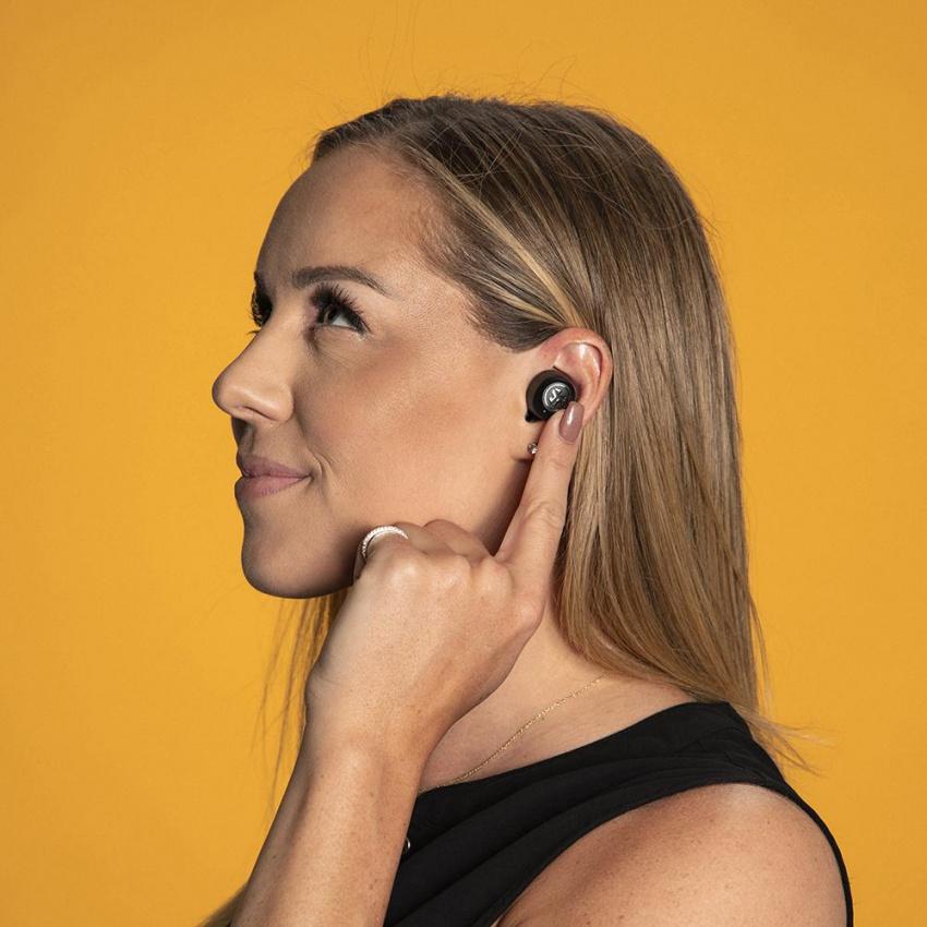 女人戴著JBuds Air ANC真無線耳塞並使用觸摸傳感器